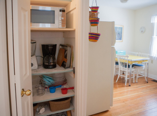 Closet with kitchen supplies and microwave