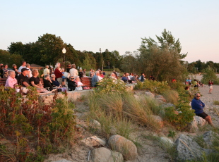 Crowd gathers to watch the sunset and listen to the Sunset Piper